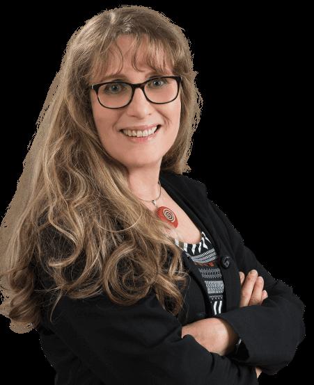 Lifekinetik ProTrainerin und OptiMind System Coach Christine Weidner. Lächelnde Dame mittleren Alters mit braunen Haaren, dunkelbrauner Brille, einer Kette mit rundem Tonstein und schwarzem Jacket. Ihre Arme sind verschränkt.