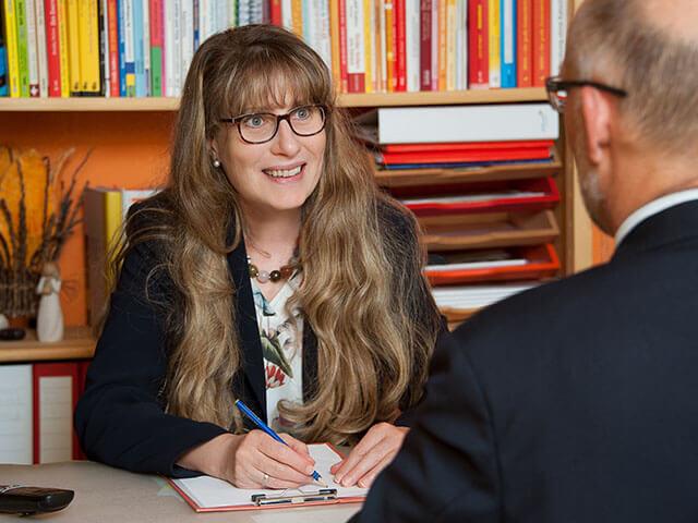 Christine Weidner macht sich in einer Coachingsituation, mit einem nicht erkennbaren Mann, Notizen.